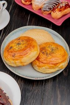 Vista lateral de productos de panadería como goghal y shakarbura en placa con tortas en madera