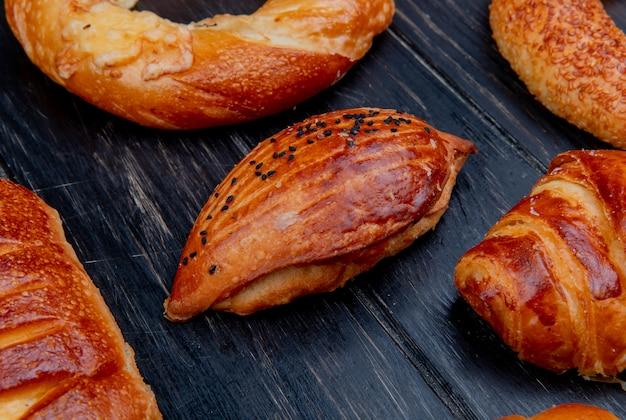Vista lateral de productos de panadería como panecillo sobre superficie de madera