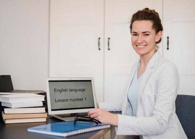 Vista lateral del profesor sonriente posando con laptop y libros para la clase en línea