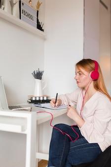 Vista lateral de la profesora con auriculares sosteniendo una clase en línea