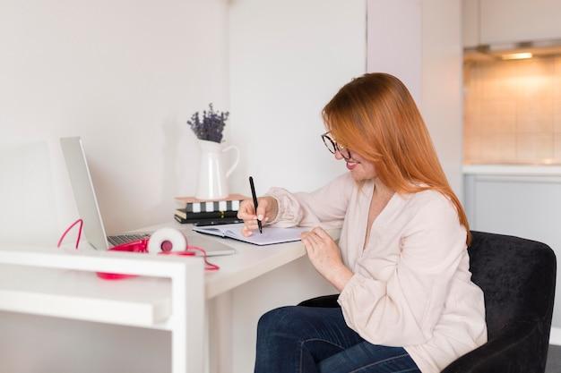 Vista lateral de la profesora durante la clase en línea en el escritorio