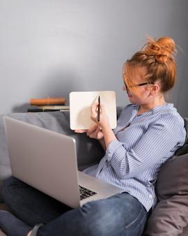 Vista lateral de la profesora en el sofá sosteniendo una clase en línea