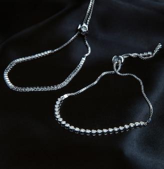 Vista lateral de pulseras de plata con diamantes en la pared negra