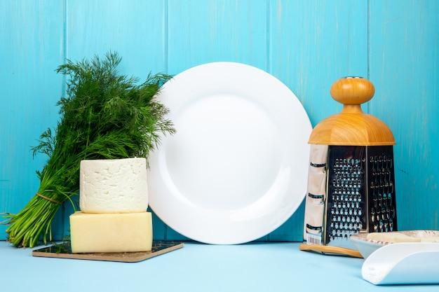Vista lateral de queso feta blanco con eneldo y rallador y plato blanco vacío en azul