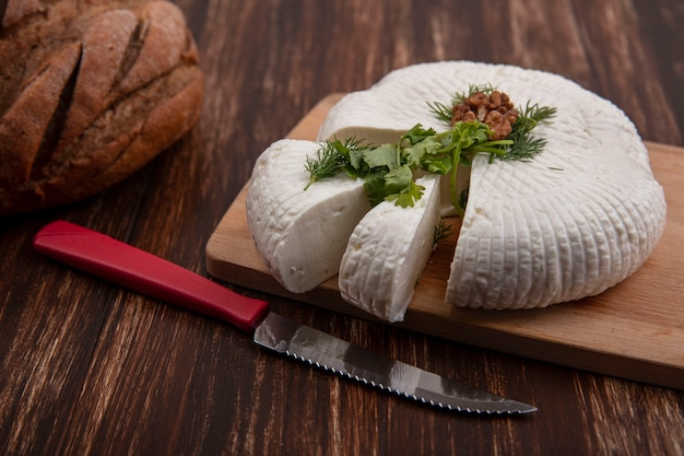 Vista lateral de queso feta sobre un soporte con un cuchillo y una hogaza de pan sobre un fondo de madera