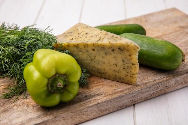 Vista lateral de queso con pepinos con pimiento sobre un soporte con eneldo sobre una placa blanca.