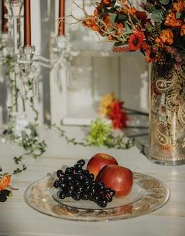 Vista lateral del racimo de uvas y manzanas en un plato con patrón buta en una mesa de madera