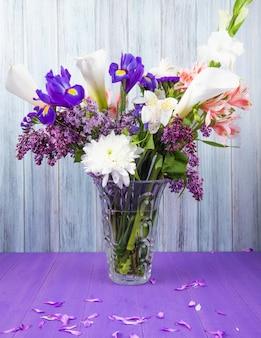 Vista lateral de un ramo de alcatraces de color blanco con iris morado oscuro gladiolo lila blanco y flores de alstroemeria rosa en un florero de vidrio sobre una superficie púrpura sobre fondo de madera gris