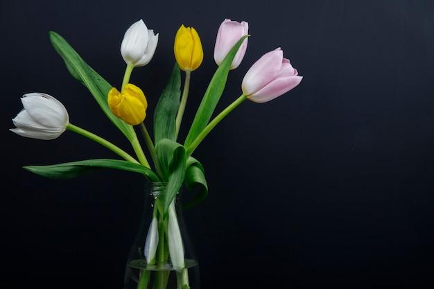 Vista lateral de un ramo de coloridas flores de tulipán en una botella de vidrio en fondo negro