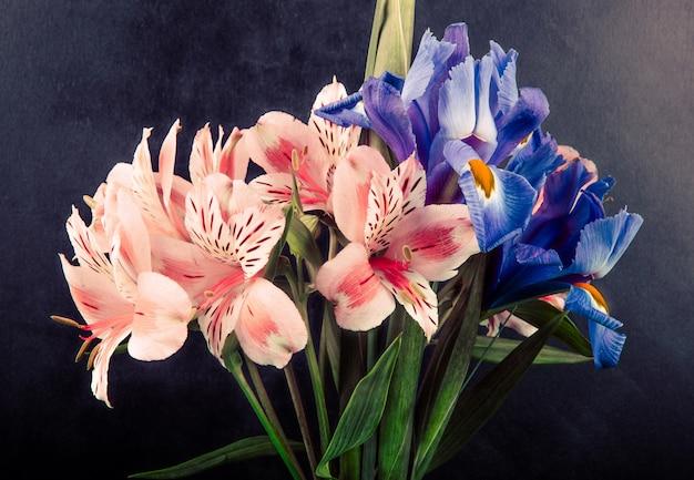 Vista lateral de un ramo de flores de alstroemeria e iris de color rosa y morado sobre fondo negro