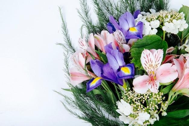 Vista lateral de un ramo de flores de color rosa alstroemeria con iris morado oscuro floreciendo viburnum y espárragos sobre fondo blanco.