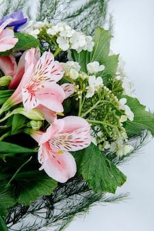 Vista lateral de un ramo de flores de color rosa alstroemeria con iris morado oscuro floreciendo viburnum sobre fondo blanco.