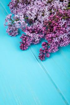 Vista lateral de un ramo de flores lilas aislado sobre fondo de madera azul con espacio de copia