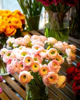 Vista lateral del ramo de flores de ranúnculo rosa en florero de vidrio en la tienda de flores