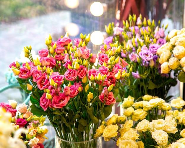 Vista lateral del ramo de rosas de aerosol de color rosa en florero de vidrio