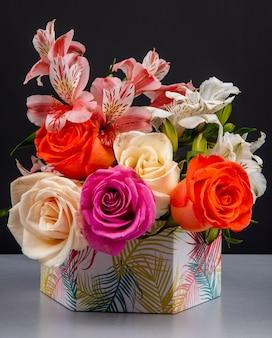 Vista lateral de un ramo de rosas coloridas y flores de alstroemeria de color rosa en una caja de regalo sobre la mesa negra