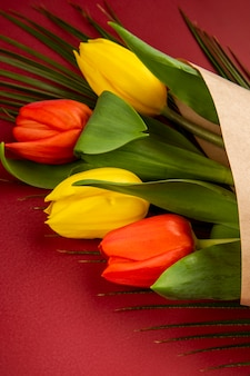 Vista lateral de un ramo de tulipanes de color amarillo y rojo en papel artesanal con hoja de palma en la mesa roja