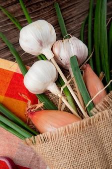 Vista lateral del ramo de verduras como chalota de ajo y cebolla verde sobre tela sobre fondo de madera