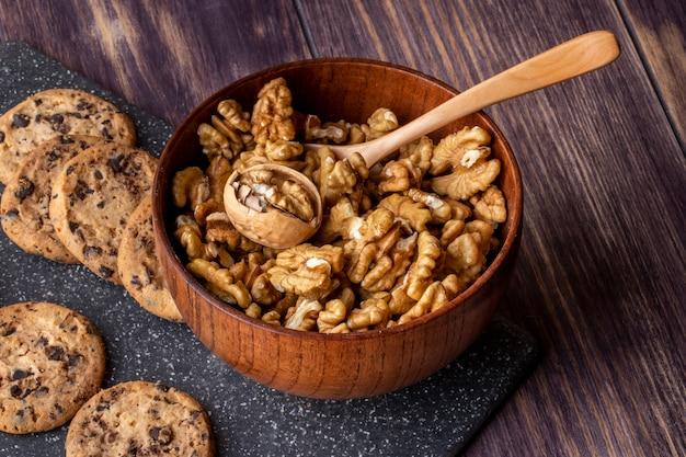 Vista lateral en un recipiente con nueces peladas con galletas de chocolate de avena en un tablero