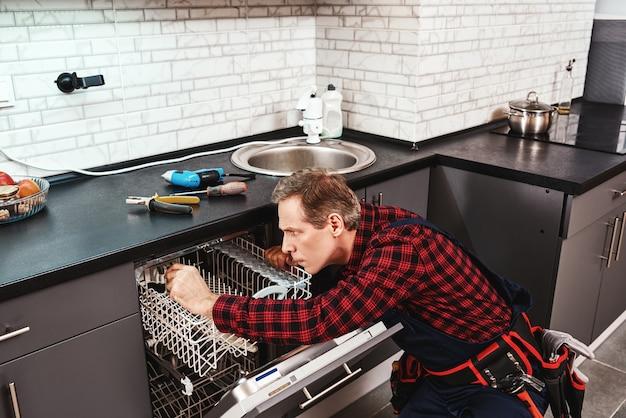 Vista lateral de la reparación de lavavajillas técnico masculino sentado cerca de lavavajillas