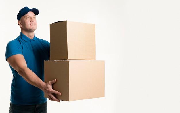 Vista lateral del repartidor con cajas de cartón en las manos