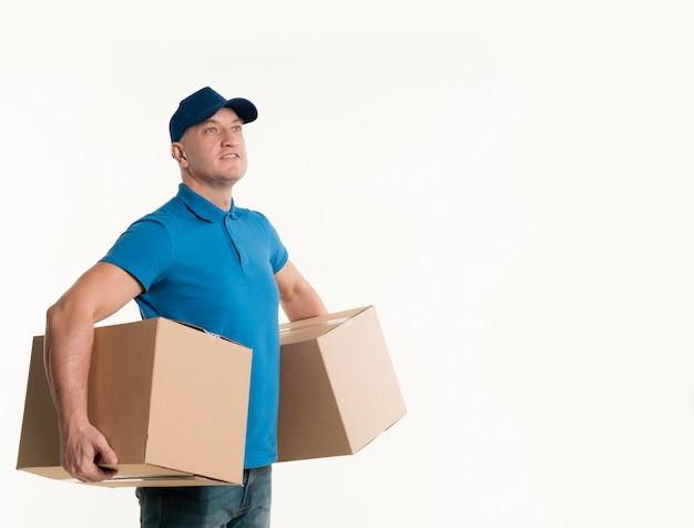 Vista lateral del repartidor feliz con cajas de cartón