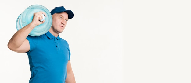 Vista lateral del repartidor llevando una botella de agua en el hombro