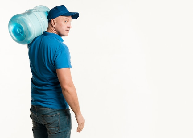 Vista lateral del repartidor llevando una botella de agua