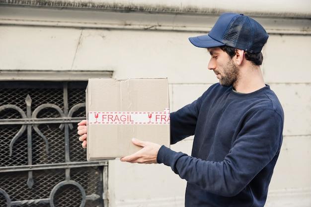 Vista lateral de un repartidor mirando el paquete