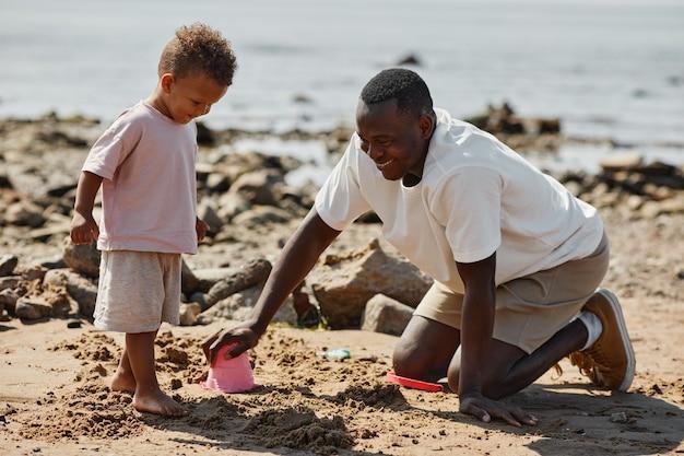 Vista lateral retrato de cuerpo entero del hombre afroamericano jugando con su hijo en la playa juntos