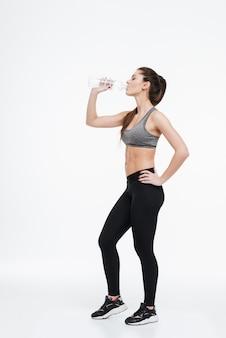 Vista lateral retrato de cuerpo entero de una joven mujer deportiva sana bebiendo de una botella de agua aislada