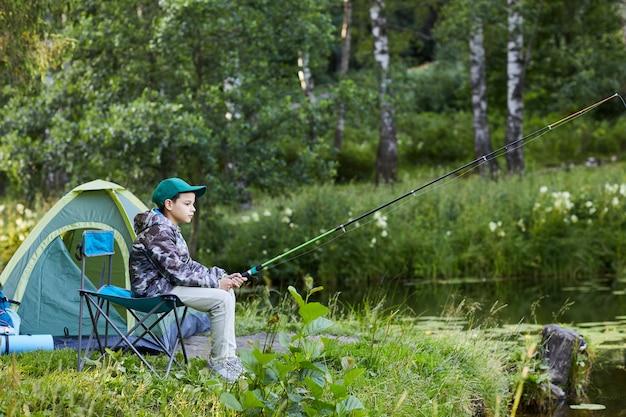 Vista lateral retrato de cuerpo entero de un joven pescando por el lago durante el viaje de campamento, espacio de copia