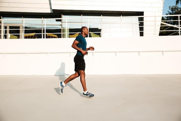 Vista lateral retrato de un deportista africano en auriculares corriendo