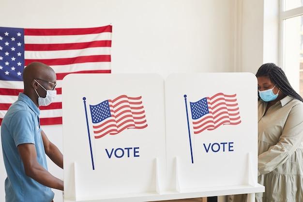 Vista lateral retrato de dos personas afroamericanas con máscaras de pie en las cabinas de votación uno frente al otro en el día de las elecciones posteriores a la pandemia