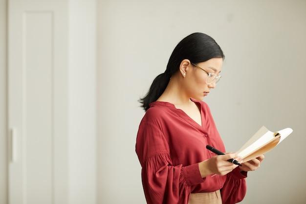 Vista lateral retrato de exitosa empresaria asiática con blusa roja leyendo notas en el portapapeles mientras está de pie contra la pared blanca en la oficina, espacio de copia