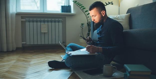 Vista lateral retrato de hombre caucásico con barba charlando con alguien en el suelo usando una computadora portátil mientras trabaja con algunos documentos