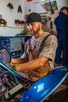 Vista lateral retrato del hombre que trabaja en el garaje reparando motocicletas