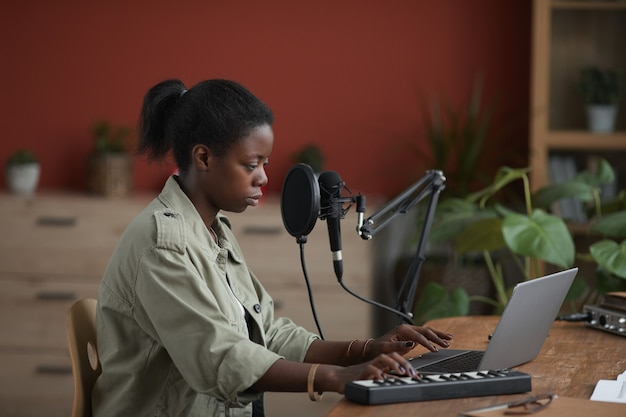 Vista lateral retrato de joven afroamericana componer música en el estudio de grabación en casa, espacio de copia