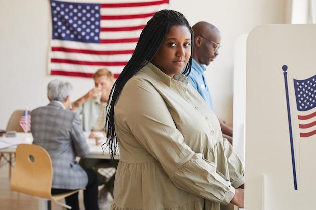 Vista lateral retrato de joven afroamericana de pie en la cabina de votación y espacio de copia