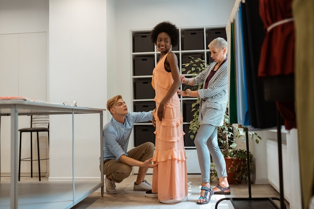 Vista lateral retrato de un modelo sonriente con un vestido nuevo de pie en un estudio.