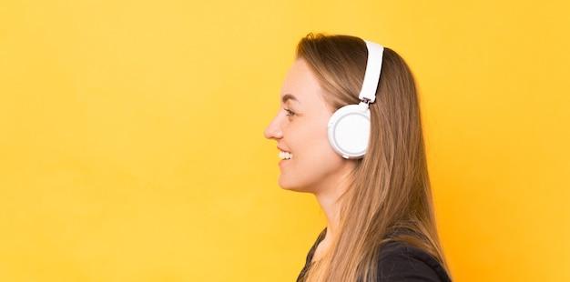 Vista lateral retrato de mujer sonriente con auriculares inalámbricos blancos sobre fondo amarillo