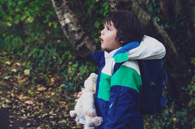 Vista lateral del retrato del niño con oso de peluche mirando cara curiosa de pie en el parque