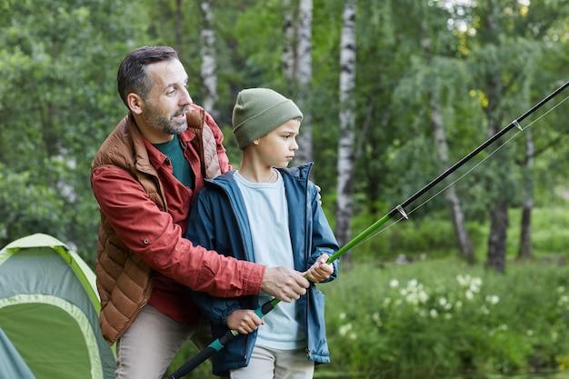 Vista lateral retrato de padre maduro enseñando a su hijo a pescar mientras disfrutan de un viaje de campamento junto al lago, espacio de copia