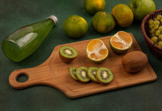 Vista lateral de rodajas de kiwi sobre una tabla de cortar con mandarinas y una botella de jugo en una pared verde