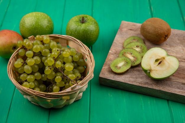Vista lateral de rodajas de kiwi en un soporte con manzanas verdes y pera con uvas verdes en una canasta sobre un fondo verde