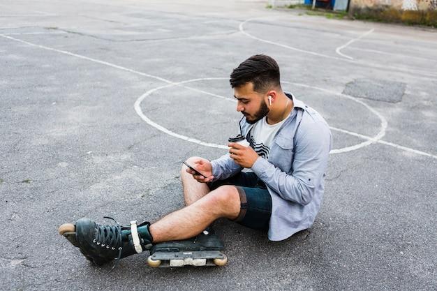 Vista lateral de un rollerskater masculino relajado que usa el teléfono móvil