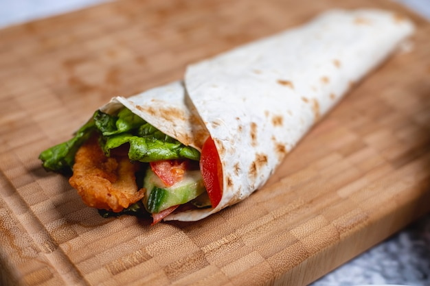 Vista lateral rollito de pollo filete de pollo frito con tomate pepino y lechuga en pita