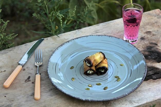 Vista lateral del rollo de berenjenas fritas con queso crema, ajo y nueces en placa al aire libre