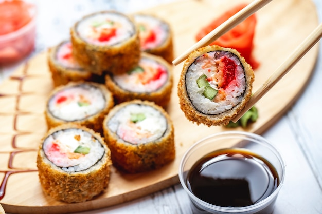 Vista lateral rollo caliente sushi frito con queso crema pepino tomate salmón jengibre y wasabi en un tablero