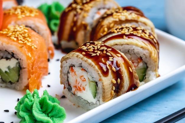 Vista lateral del rollo de filadelfia con congrio de crema de congrio, pepino, salsa teriyaki y wasabi en un plato